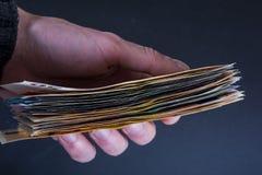 Main humaine jugeant des billets de banque d'argent-euro d'isolement sur un fond gris-foncé Photographie stock libre de droits