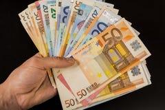 Main humaine jugeant des billets de banque d'argent-euro d'isolement sur un fond gris-foncé Image stock