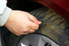 Main humaine perçant la roue de pneu Photographie stock libre de droits