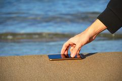 Main humaine prenant le téléphone intelligent imperméable sur le sable images stock