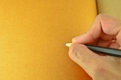 Main humaine retenant un crayon Images libres de droits