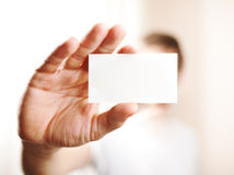 Main humaine tenant la carte de visite professionnelle vierge de visite Photographie stock libre de droits