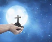 Main humaine tenant la croix chrétienne avec le sol sur la main Photos stock