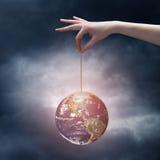 Main humaine tenant la planète de la terre sur la corde Image stock