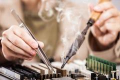 Main humaine tenant le fer à souder réparant le boa de circuit d'ordinateur Image stock