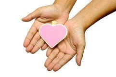 Main humaine tenant le signe en bois de forme de coeur Photos stock