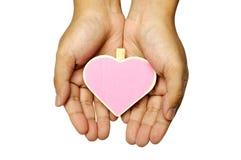 Main humaine tenant le signe en bois de forme de coeur Image libre de droits