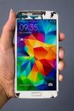 Main humaine tenant le smartphone cassé de Samsung Note2 Photographie stock