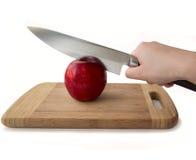 Main humaine tenant un couteau et une pomme rouge Image libre de droits