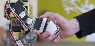 Main humaine tenant une main de robot avec une poignée de main Image stock