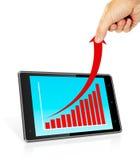 Main humaine tirant vers le haut la flèche rouge du PC de tablette Photos libres de droits