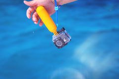 Main humide tenant la caméra d'action dans le cas imperméable photographie stock libre de droits