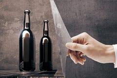 Main indiquant les bouteilles à bière vides Photographie stock libre de droits
