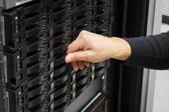Main informatique du ` s d'ingénieur remplaçant l'unité de disque dur au centre de traitement des données image stock