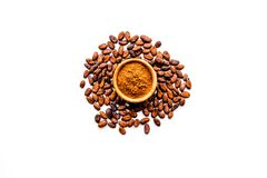 Main ingredient for chocolate. Cocoa powder in bowl near cocoa beans on white background top view copy space. Main ingredient for chocolate. Cocoa powder in bowl stock photography
