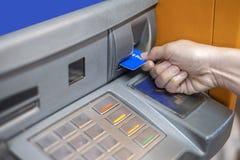 Main insérant la carte de distributeur bancaire dans la machine de banque d'atmosphère pour retirer l'argent photographie stock libre de droits