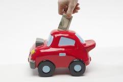 Main insérant la note du dollar en Toy Car Photographie stock