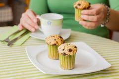 Main intéressante de fille prenant le petit pain de puce de chocolat au petit déjeuner Photos stock