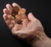 Main jetant des pièces de monnaie en l'air Photo libre de droits