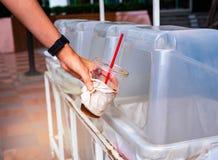 Main jetant la tasse de café en plastique vide dans le bac de recyclage image stock