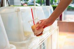 Main jetant la tasse de café en plastique vide dans le bac de recyclage photos libres de droits