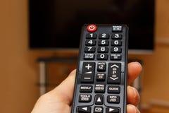 Main jugeant à télécommande pour la télévision Photo stock