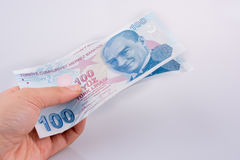 Main jugeant 100 billets de banque de Lire de Turksh disponibles Image stock