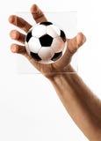 Main jugeant en verre avec la bande dessinée de ballon de football photos stock