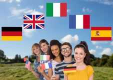 main language flags around group teenagers with flags in field Royalty Free Stock Photos
