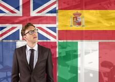 Main language flags around young businessman thinking. office background. Digital composite of main language flags around young businessman thinking. office Royalty Free Stock Image