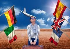 Main language flags around young woman with suitcase. field background with plane Royalty Free Stock Image