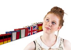 Main language flags suitcases behind young happy woman Stock Photo
