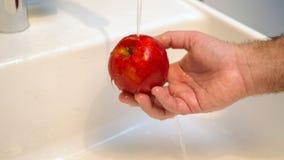Main lavant une pomme rouge dans l'évier Image libre de droits