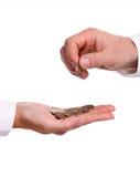 Main mâle donnant une euro pièce de monnaie à une autre personne Photos stock
