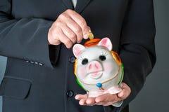 Main mâle mettant la pièce de monnaie dans une tirelire Image libre de droits
