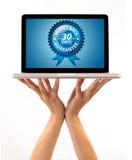 Main mâle retenant un ordinateur portatif avec l'étiquette de dos d'argent Image stock