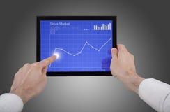 Main mâle retenant un PC de touchpad, contrôlant des stocks Photos libres de droits