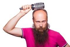 Main malheureuse adulte d'homme tenant le peigne sur la tête chauve photo stock