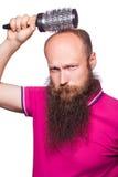 Main malheureuse adulte d'homme tenant le peigne sur la tête chauve Photographie stock libre de droits