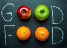 Main marquant avec des lettres la bonne nourriture sur le tableau noir avec des pommes de rouge de vert d'oranges de fruits Vegan image stock
