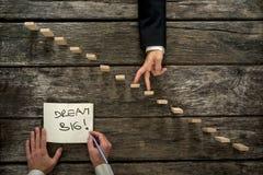 Main masculine écrivant un rêve d'une manière encourageante de message grand dans un bloc-notes Images stock
