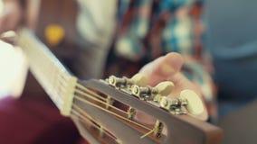 Main masculine accordant le mouvement lent de plan rapproché de guitare acoustique banque de vidéos