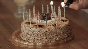 Main masculine allumant des bougies dans le gâteau d'anniversaire Image stock