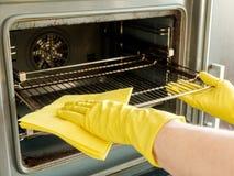 Main masculine avec des gants nettoyant le four Photographie stock