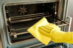 Main masculine avec des gants nettoyant le four images libres de droits