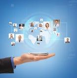 Main masculine avec le smartphone au-dessus des icônes des contacts image libre de droits