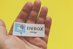Main masculine avec un morceau de papier et du mot : Message de boîte de réception photo stock
