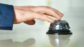 Main masculine d'invité sonnant à la réception la cloche argentée de table au plan rapproché d'hôtel de vintage clips vidéos