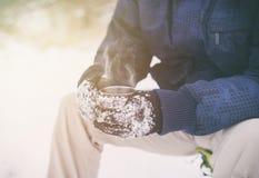 Main masculine dans les gants tenant la tasse avec le thé ou le café chaud Pause caf? Concept d'horaire d'hiver images libres de droits