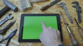 Main masculine de l'artisan d'artisan à l'aide du PC de comprimé avec l'écran vert dans l'atelier Vue supérieure Mensonge différe clips vidéos